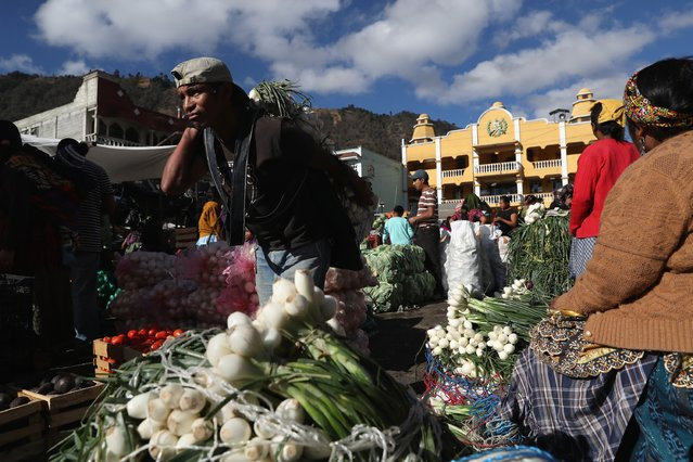 A porter carries a load of onions through a vegetable market on February 11, 2017 in Almolonga, Guatemala. (Photo by John Moore/Getty Images)
