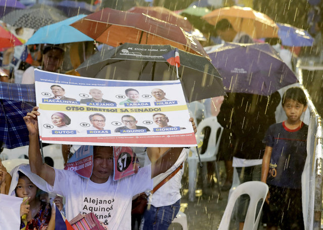 In this Wednesday, May 8, 2019, photo, supporters brave the rain during the last campaign rally together by the opposition senatorial candidates in suburban Quezon city, northeast of Manila, Philippines. (Photo by Bullit Marquez/AP Photo)