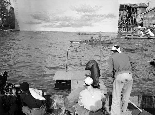 """A scene from """"Battleship Yamato"""" is filmed in the studio pool of Japan's Shin-Toho Motion Picture Company on June 8, 1953. The background of sky and water ends at left and right, a camera crew in the foreground. (Photo by Yuichi Ishizaki/AP Photo via The Atlantic)"""