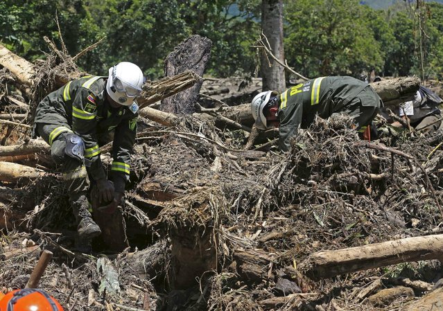 Colombian policemen look for the bodies of victims of a landslide that sent mud and water crashing onto homes close to the municipality of Salgar in Antioquia department, Colombia May 19, 2015. (Photo by Jose Miguel Gomez/Reuters)