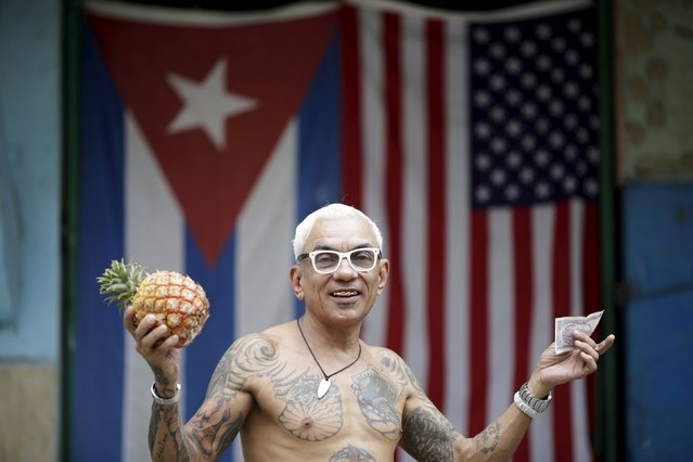 "Zamora, 55, self-employed, poses for a photograph in front of the Cuban and U.S. flags after buying a pineapple in Havana, March 25, 2016. Regarding Obama's historic visit to the island, Zamora said ""It's good for the Cubans that he came and re-established relationships between the two countries"". (Photo by Ueslei Marcelino/Reuters)"