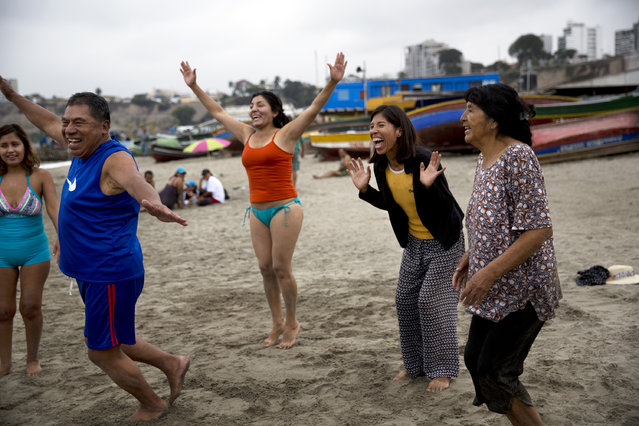 In this May 8, 2015 photo, people smile during a laugh therapy session on Fishermen's Beach in Lima, Peru. Natural therapy promoter Jose Cusquisiban organizes therapy groups and has his patients jog barefoot on the beach sand. (Photo by Rodrigo Abd/AP Photo)