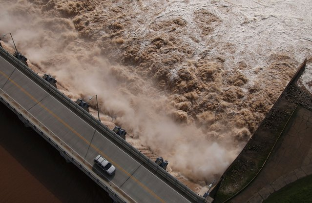 Water is released from the Keystone Dam into the Arkansas River northwest of Tulsa, Okla., Friday, May 24, 2019. The U.S. Army Corps of Engineers began increasing the amount of water being released from the dam on Friday to control the flooding. (Photo by Tom Gilbert/Tulsa World via AP Photo)