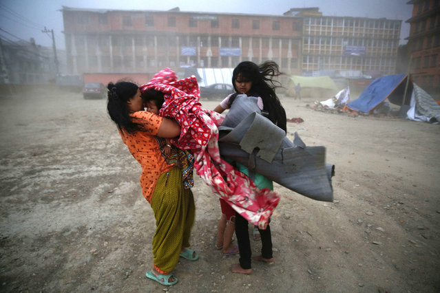 A storm whips through a tented area occupied by Nepalese earthquake survivors as a mother grabs her infant child and runs to find shelter in Kathmandu, Nepal 23 May 2015. Nepalese, who lost their homes in earthquake and fear aftershocks, have been living in temporary shelter in open ground which they had to flee because of the heavy rain and powerful wind. (Photo by Narendra Shrestha/EPA)