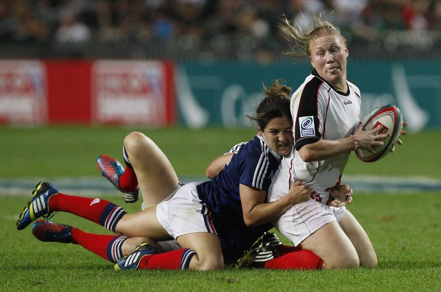 Canada's Mandy Marchak (R) is taken down by France's Pauline Biscarat during the final match of the Hong Kong Sevens rugby women's invitational cup in Hong Kong March 28, 2014. (Photo by Tyrone Siu/Reuters)
