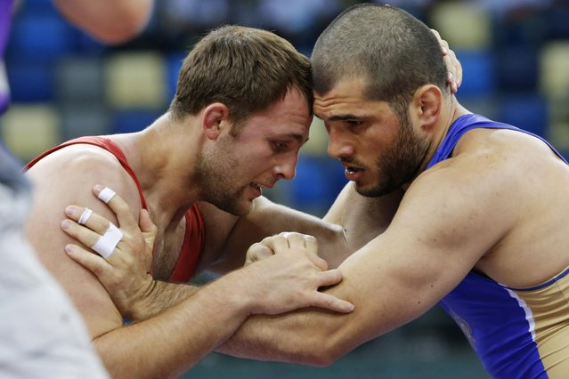 Islam Magomedov of Russia, right, and Dimitriy Timchenko of Ukraine compete in the the Men's wrestling, 98kg Greco-Roman Gold medal event at the 2015 European Games in Baku, Azerbaijan, Saturday, June 13, 2015. (AP Photo/Dmitry Lovetsky)