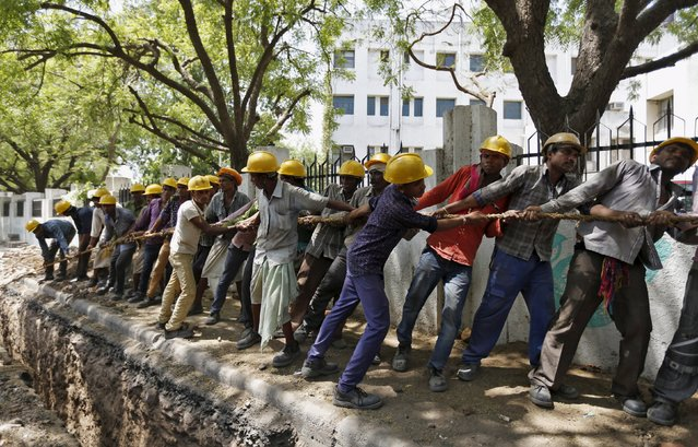 Labourers pull a rope as they lay a high voltage electricity cable underground along a roadside in Ahmedabad, India, April 19, 2016. (Photo by Amit Dave/Reuters)