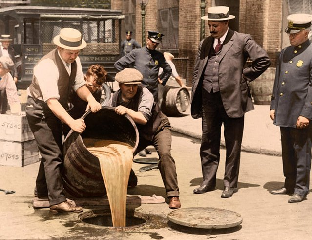 New York City Deputy Police Commissioner John A. Leach, right, watching agents pour liquor into sewer following a raid during the height of prohibition, circa 1921. (Photo by Tom Marshall/Mediadrumworld)