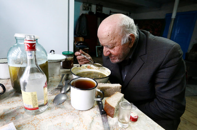 """Ivan Shamyanok, 90, eats lunch in his house in the village of Tulgovichi, near the exclusion zone around the Chernobyl nuclear reactor, Belarus April 2, 2016. Shamyanok says he doesn't have any problems with his health, but takes medication sometimes and drinks a small glass of vodka before meals """"to help the appetite"""". A mobile shop operating out of the back of a car visits the village twice a week and on Saturdays Shamyanok's granddaughter comes to cook food for the week and clean his house. (Photo by Vasily Fedosenko/Reuters)"""