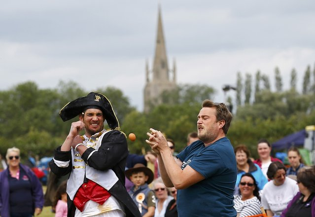 A man in fancy dress reacts as a competitor drops an egg during the World Egg Throwing Championships and Vintage Day in Swaton, Britain June 28, 2015. (Photo by Darren Staples/Reuters)
