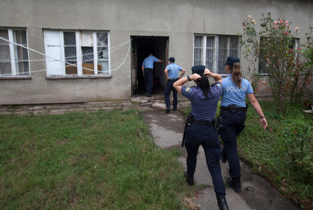 Police enter the house where a suspect killed six people, including a ten-year-old child, before committing suicide, in Zagreb, Croatia, Friday, August 2, 2019. Croatian police identified the killings Friday as domestic violence. (Photo by Nikola Solic/AP Photo)