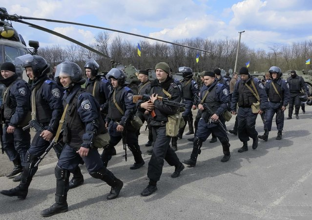 """Members of the Ukrainian Interior Ministry walk past a MI-8 military helicopter and armored personnel carriers at a checkpoint near the town of Izium, eastern Ukraine, April 15, 2014. Russia declared Ukraine on the brink of civil war on Tuesday as Kiev said an """"anti-terrorist operation"""" against pro-Moscow separatists was under way, with troops and armored personnel carriers seen near a flashpoint eastern town. (Photo by Dmitry Madorsky/Reuters)"""