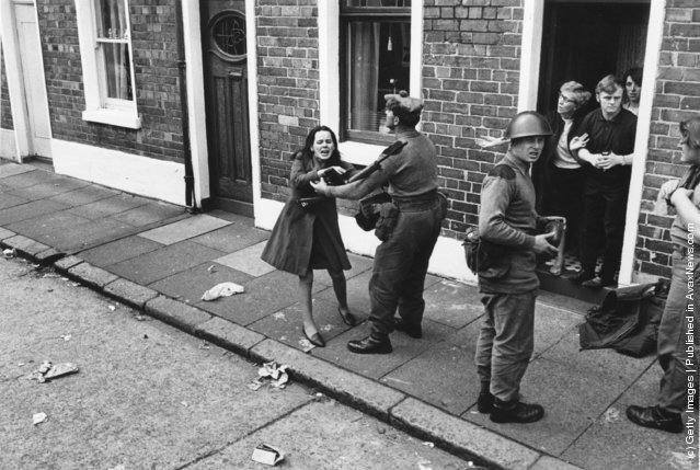 Armed British soldiers restrain a young civilian in the streets of Belfast, 1970