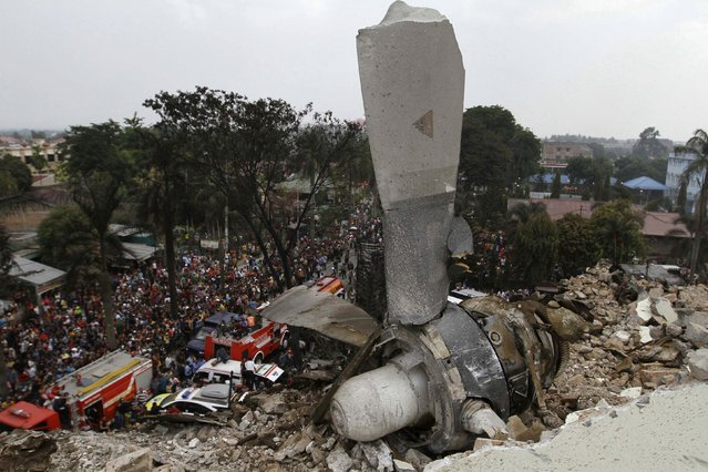A propeller from an Indonesian military C-130 Hercules transport plane rests on the roof of a building after the plane crashed into a residential area in the North Sumatra city of Medan, Indonesia, June 30, 2015. (Photo by Roni Bintang/Reuters)
