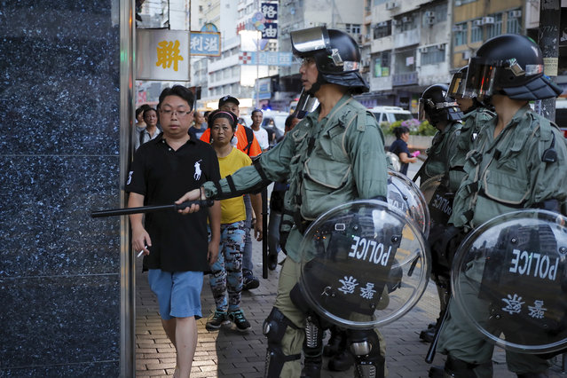 Riot policemen stop people as they face off with protesters during the anti-extradition bill protest in Hong Kong, Sunday, August 11, 2019. (Photo by Kin Cheung/AP Photo)