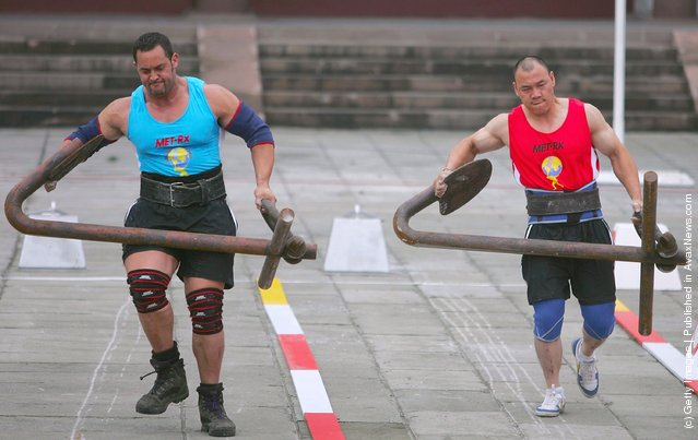 Carl Waitanen of New Zealand (L) and Gu Yanli of China carry anchors during a match of the 2005 World's Strongest Man Competition at Wuhou Temple