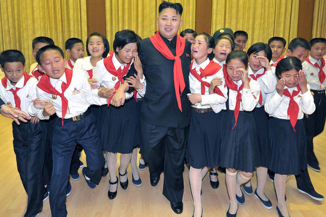 This photo released by North Korea's official Korean Central News Agency (KCNA) on June 7, 2012 shows North Korean leader Kim Jong-Un (C) surrounded by members of the Korean Children's Union (KCU) organizations during a joint national meeting to celebrate the 66th anniversary of the KCU organizations at Kim Il-Sung Stadium in Pyongyang on June 6, 2012. (Photo by AFP Photo/KCNA via KNS)