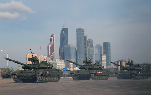 """Russian servicemen sit atop of Russian T-90A main battle tanks before a rehearsal for the Victory Day parade, with the Moscow International Business Center also known as """"Moskva-City"""" seen in the background, at a range in Moscow, Russia, May 5, 2016. (Photo by Maxim Shemetov/Reuters)"""