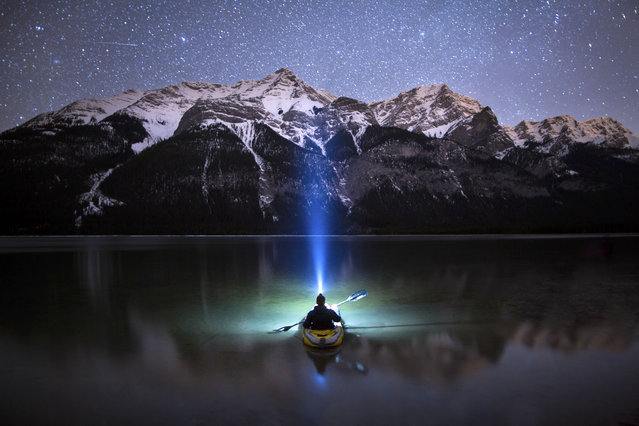Paul Zizka Drifts across a lake in the Canadian Rockies a beam from his head lamp shooting up into the night sky in the Canadian Rockies. (Photo by Paul Zizka/Caters News Agency)