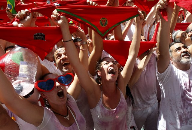"""Revellers hold up traditional red scarves during the start of the San Fermin festival in Pamplona July 6, 2015. San Fermin festival, best known for its daily running of the bulls, kicked off today with the traditional """"Chupinazo"""" ocket launch and will run until July 14. (Photo by Reuters/Stringer)"""