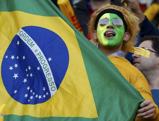 A Brazil fan holds the national flag ahead of the Copa America 2015 quarter-finals soccer match against Paraguay at Estadio Municipal Alcaldesa Ester Roa Rebolledo in Concepcion, Chile, June 27, 2015. (Photo by Mariana Bazo/Reuters)