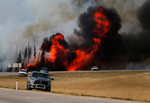 Smoke and flames from the wildfires erupt behind cars on the highway near Fort McMurray, Alberta, Canada, May 7, 2016. (Photo by Mark Blinch/Reuters)