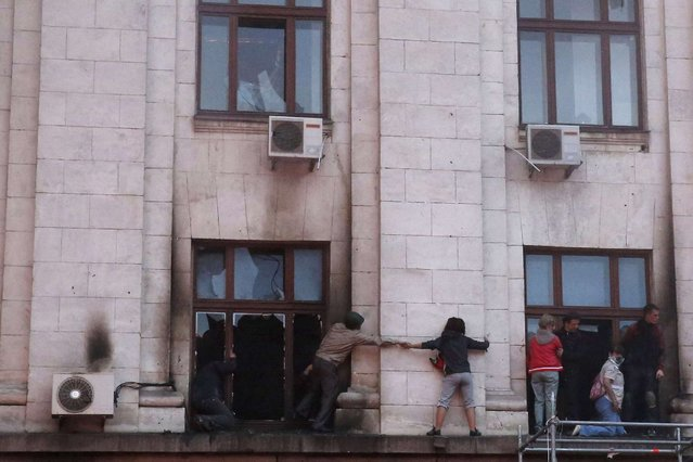 People wait for rescue on an upper storey ledge during a fire at the trade union building in Odessa May 2, 2014. At least 38 people were killed in a fire on Friday in the trade union building in the centre of Ukraine's southern port city of Odessa, regional police said. (Photo by Yevgeny Volokin/Reuters)