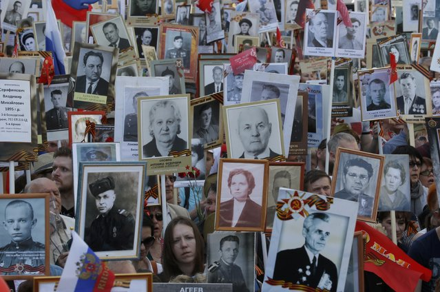 People hold pictures of World War Two soldiers as they take part in the Immortal Regiment march during the Victory Day celebrations, marking the 71st anniversary of the victory over Nazi Germany in World War Two, in central Moscow, Russia, May 9, 2016. (Photo by Sergei Karpukhin/Reuters)