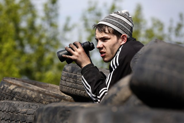 A pro-Russian activist holds binoculars at a checkpoint manned by pro-Russian separatists near the southern Ukrainian city of Slavyansk on May 3, 2014. Ukrainian soldiers and pro-Russian rebels fought fierce battles todayaround a flashpoint town, with only a small reprieve to allow passage of a freed team of OSCE inspectors. More than 50 people have died in two days of clashes nationwide – most of them in a horrific inferno amid street clashes in the southern city of Odessa. (Photo by Max Vetrov/AFP Photo)