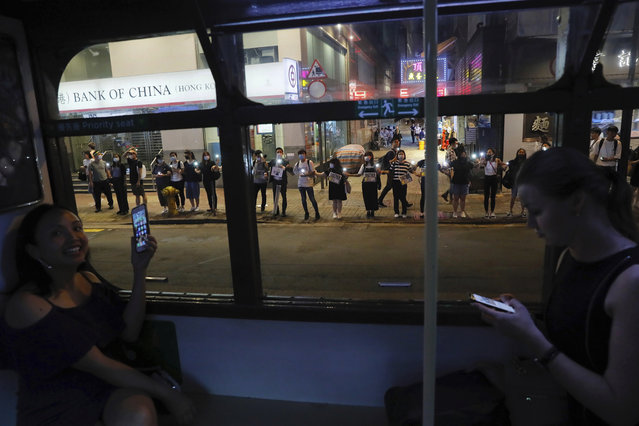 Demonstrators, seen from inside a tram, link hands along a street in Hong Kong, Friday, August 23, 2019. Supporters of Hong Kong's pro-democracy movement created human chains on both sides of the city's harbor Friday, inspired by a historic protest 30 years ago in the Baltic states against Soviet control. (Photo by Kin Cheung/AP Photo)
