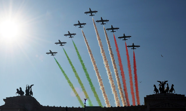 """Green, white and red smoke in the colours of the Italian flag are left in the air over the Vittorio Emanuele monument by the Italian Air Force aerobatic unit """"Frecce Tricolori"""" marking the anniversary of Italian national unification on March 17, 2014 in Rome. (Photo by Vincenzo Pinto/AFP Photo)"""
