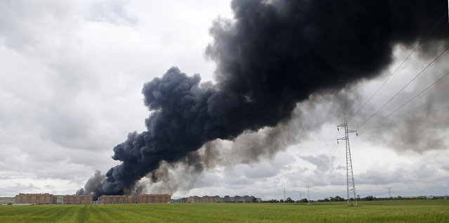 Billowing black smoke rises from behind large housing blocks in Sesena, central Spain, Friday, May 13, 2016. A massive fire is raging at a sprawling tire dump in a town near Madrid, sending a spectacular cloud of thick black smoke into the air that's visible for at least 30 kilometers (20 miles). Ten teams of firefighters are trying to put out the blaze at the tire dump in the town of Sesena, still raging more than 10 hours after it started. (Photo by Paul White/AP Photo)