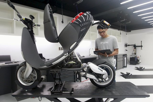 A mechanic examines a Gogoro Smartscooter which is connected to a tablet, in its shop in Taipei, Taiwan, July 6, 2015. (Photo by Pichi Chuang/Reuters)