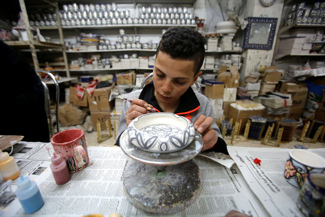 A Palestinian boy paints ceramics in Al-Okhowa pottery shop in the West Bank city of Hebron February 9, 2017. (Photo by Mussa Qawasma/Reuters)