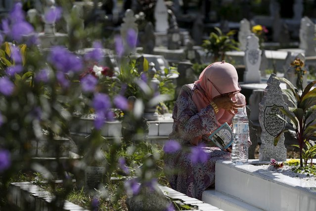 A woman cries as she recites the koran at the grave of a relative on Eid Al-Fitr in Kuala Lumpur, Malaysia, July 17, 2015. (Photo by Olivia Harris/Reuters)