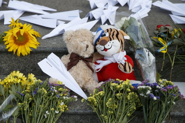 Flowers, toys and self-made paper planes are left to commemorate the victims of the Malaysia Airlines flight MH17 plane crash a year ago outside the Dutch embassy in Kiev, Ukraine, July 17, 2015. (Photo by Valentyn Ogirenko/Reuters)