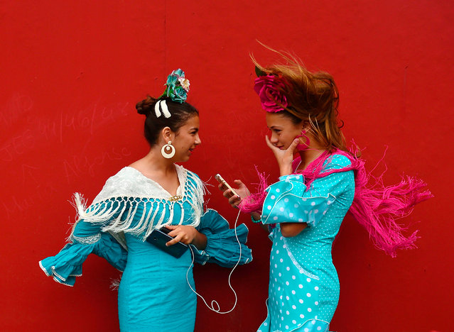 "Two girls wearing traditional Sevillian dresses talk during the ""Feria de Abril"" (April Fair) in Sevilla on April 30, 2017. The fair dates back to 1847 when it was originally organized as a livestock fair but has turned into a week of flamenco dancing, music and bullfighting. (Photo by Cristina Quicler/AFP Photo)"