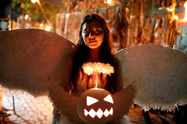 "A girl dressed as an angel, participates in a parade called ""La Calabiuza"" on the eve of the Day of the Dead in Tonacatepeque, November 1, 2019. (Photo by Jose Cabezas/Reuters)"