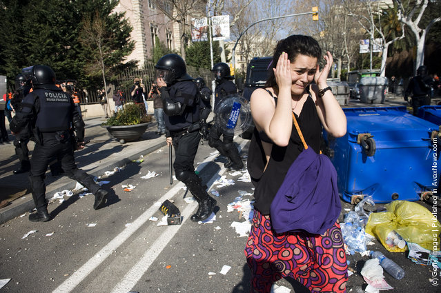 A student runs for cover as riot police clash with students during a demonstration on February 29, 2012 in Barcelona