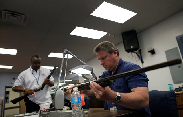 """Chicago Police officers examine guns turned in from the public to be cataloged as part of the """"Gun Turn-in"""" event where a gift card is given for every firearm turned over to police at Universal Missionary Baptist Church in Chicago, Illinois, U.S. May 28, 2016. (Photo by Jim Young/Reuters)"""