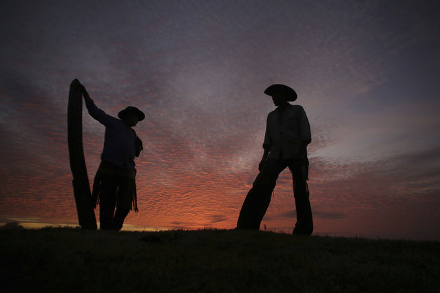 In this May 18, 2017 file photo, Joao Aquino Pereira, right, talks with fellow cowboy Rene Almeida at dawn in Corumba, in the Pantanal wetlands of Mato Grosso do Sul state, Brazil. As of Wednesday, November 6 2019, fires in Brazil's Pantanal wetlands have ripped through the biodiverse region, consuming 15,000 football fields of vegetation in just the past 10 days, burning some animals alive and sending others fleeing. (Photo by Eraldo Peres/AP Photo/File)