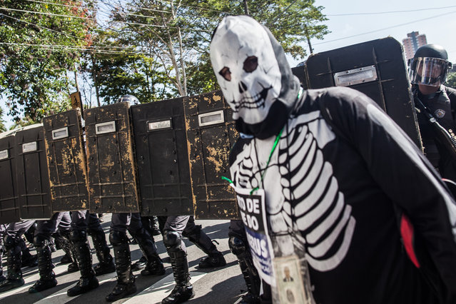 A demonstrator stands in front of police during a World Cup protest on the opening day of the event on June 12, 2014 in Sao Paulo, Brazil. Military police responded to the protest and there were reported injuries. This is the first day of the FIFA World Cup. (Photo by Victor Moriyama/Getty Images)