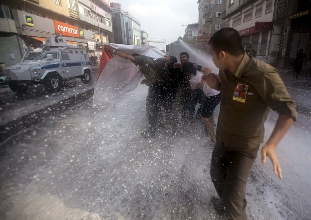 Turkish police use water cannon to disperse demonstrators during a funeral ceremony for Gunay Ozarslan, a member of the far-left People's Front who, according to local media reports, was killed by Turkish police during a security operation on Friday, in Istanbul, Turkey July 25, 2015. Turkish Prime Minister Ahmet Davutoglu said on Friday that security operations against Islamic State, as well as leftist and Kurdish militants, were not a one-off but were comprehensive and would continue. (Photo by Huseyin Aldemir/Reuters)