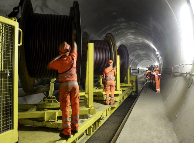 In this October 31, 2013 file photo construction workers are busy in the NEAT Gotthard Base Tunnel between Biasca and Amsteg, Switzerland.  The celebrations of the opening of the Gotthard  Base Tunnel  will start on June 1, 2016. (Photo by Karl Mathis/Keystone via AP Photo)
