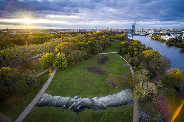 """This handout picture released on November 05, 2019 by Saype and Valentin Flauraud shows a giant biodegradable land art painting by French-Swiss artist Saype representing two hands clasped together in the Treptower Park in Berlin on November 2, 2019, part of his """"Beyond Walls"""" project. The project, which is expected to unfold over 3 years, will see Saype creating his land """"frescoes"""" in 20 cities worldwide. The project, according to his website, aims """"to create the largest human chain in the world, generate a real social movement and invite the crowds to benevolence"""". (Photo by Valentin Flauraud/AFP Photo)"""
