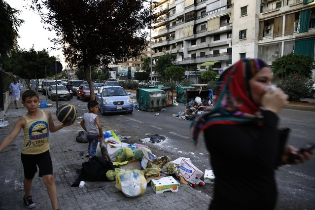 A Lebanese woman covers her nose from the smell as she walks on a street partly covered by piles of garbage in Beirut, Lebanon, Sunday, July 26, 2015. Protesters have closed the highway linking Beirut with southern Lebanon over the country's trash crisis. (Photo by Hassan Ammar/AP Photo)