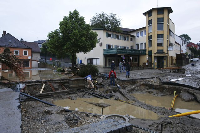 People walk in the street damaged by floods in the Bavarian village of Simbach am Inn east of Munich, Germany, June 1, 2016. (Photo by Michaela Rehle/Reuters)
