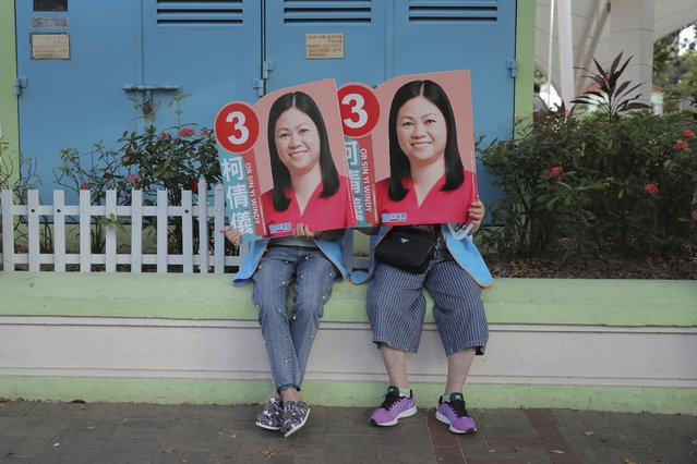 Supporters of pro China candidate Or Sin-yi Windy hold her promotional placards in Hong Kong, Sunday, November 24, 2019. Long lines snaked around plazas and extended for blocks as citizens of the semi-autonomous Chinese territory turned out in droves Sunday for an election seen as a test of public support for anti-government protests that have persisted for more than five months. (Photo by Kin Cheung/AP Photo)