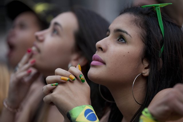 Fans watch a live telecast of the Mexico vs. Brazil match at the FIFA Fan Fest during the 2014 soccer World Cup in Sao Paulo, Brazil on June 17, 2014. (Photo by Dario Lopez-Mills/AP Photo)