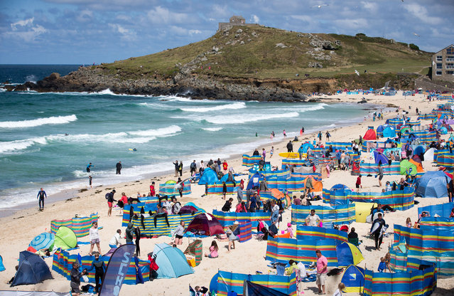 Holidaymakers enjoy the fine sunny weather at Porthmeor Beach in St Ives on July 29, 2015 in Cornwall, England. After a unsettled start to the school summer holidays, forecasters are predicting a return to more settled weather for what is the busiest period for UK holiday venues and tourist attractions. (Photo by Matt Cardy/Getty Images)